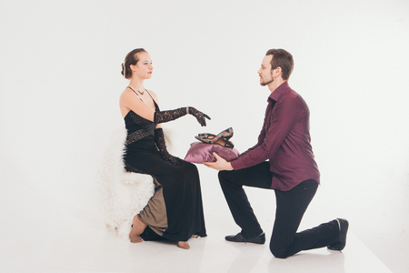 a man puts the girl on his feet shoes. Couple in a suit and dress on white background. A gift for the woman Stock fotó