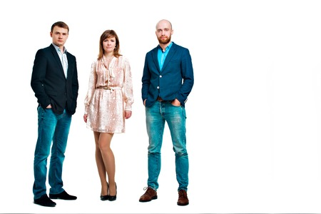 Business development concept: three people looking forward on a white background. Three attractive business people in suits stand next to each other all facing forward Reklamní fotografie