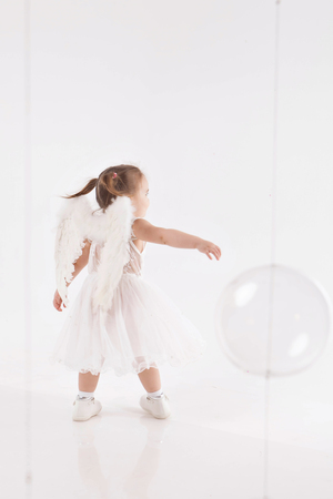 little girl in white dress with wings playing on white background