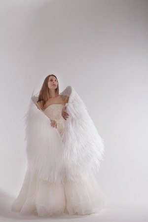 Girl in white dress with angel wings on white background. Angel-woman