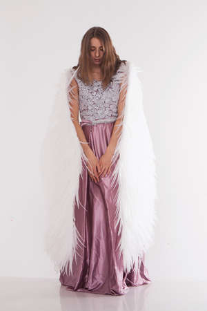 Girl in pink dress with angel wings on white background. Angel-woman
