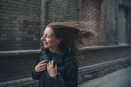 beautiful girl walking down the street in a coat, the wind waving her hair