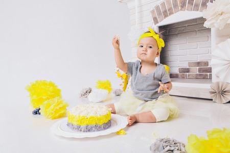 a little girl eats cake with her hands on the background of fireplace.