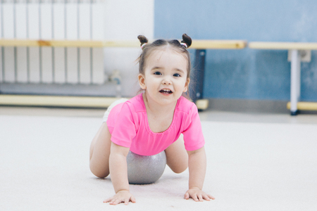 a little girl in a pink swimsuit doing gymnastics with a small ball Imagens