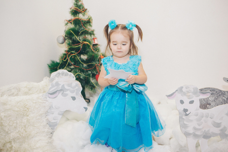a little girl in a blue dress celebrates the new year: a child among the snow of cotton wool, painted sheep, Christmas tree and stars Stock Photo