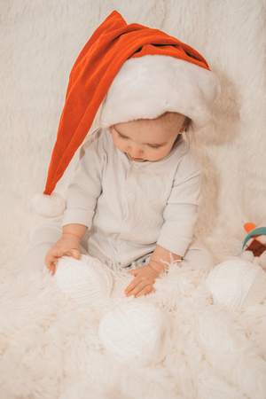 baby sleeps in a Christmas hat. Stock Photo