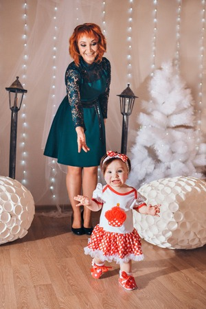 a little girl with woman near the lampposts and Christmas tree on the background of bright lights