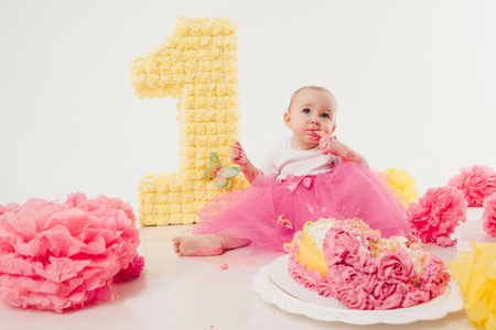 a little girl eats cake with her hands. The baby was covered in food. isolated white background. birthday party Stock Photo