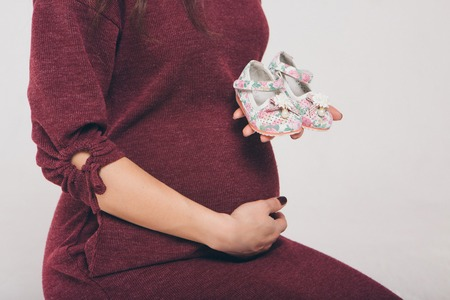 pregnant woman holding baby booties on the belly. fashion for newborns. Childrens shoes advertising