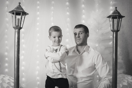 a little boy with man near the lampposts and Christmas tree on the background of bright lights