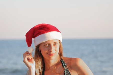 girl in a swimsuit and a red Christmas hat on the background of the sea holding a white pompom