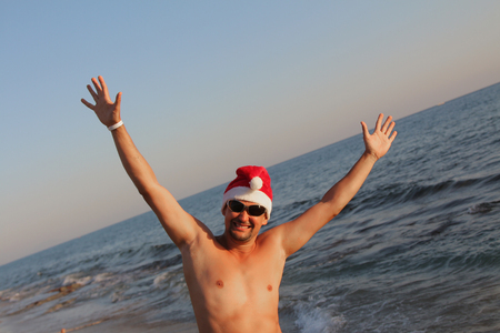 a man in a red Christmas hat and sunglasses with his hands up against the sea