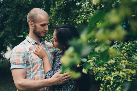 couple in love hugs an the green foliage. Man and woman smiling. Valentines day