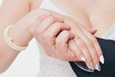hands close-up: a man holding a womans hand. Valentines day: bride and groom Stock Photo