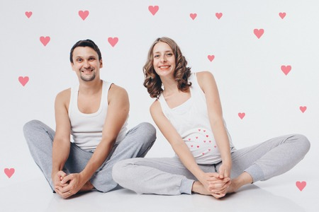 Family portrait: husband and pregnant wife sitting on the floor on a white background. a pregnant couple in love. Valentines day heart pattern 免版税图像