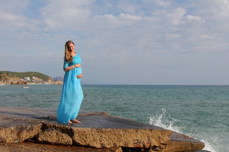 pregnant girl in blue dress on stones by the sea Stock Photo