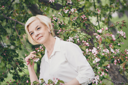 portrait of a beautiful blonde with short hair among flowers