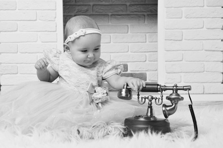 a little girl in a white dress sitting by the fireplace next to an old phone Stock Photo