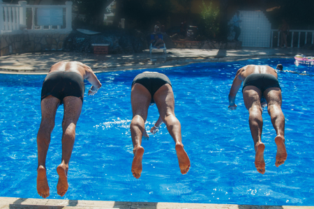 rear view: three man jumps into the pool. Swimmers in the water