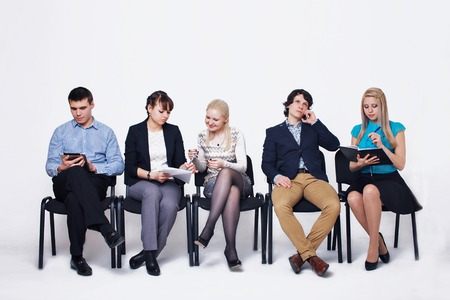 business people waiting in queue sitting in row holding smartphones and cvs, human resources, employment and hiring concept Imagens