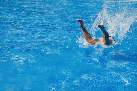 a man jumps into the pool. Swimmer in the water Stock Photo