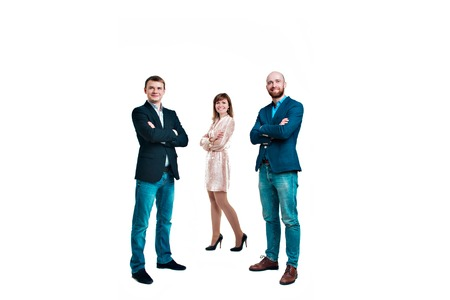 Business development concept: three people looking forward on a white background. Three attractive business people in suits stand next to each other all facing forward