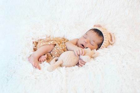pasgeboren baby slaapt met een speeltje naast de gebreide teddybeer