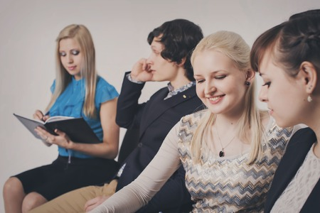 business people waiting in queue sitting in row holding smartphones and cvs, human resources, employment and hiring concept Stock Photo