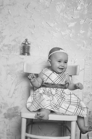 a little girl in a dress sits on a chair and smiles