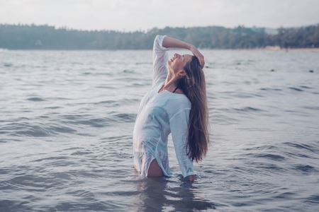 girl with long hair in white shirt posing in water