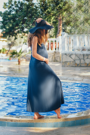 pregnant woman with long hair in blue dress posing in water Imagens