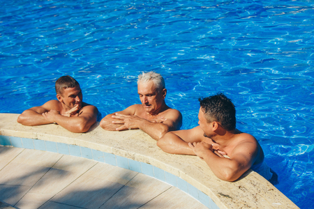 a group of men swimming in the pool