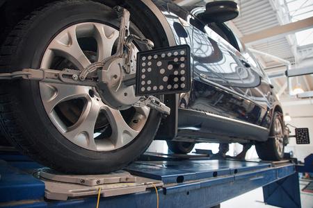 réparation de voiture : gros plan de remplacement de roue. mécanicien vissant ou dévissant la roue de la voiture au garage de service automobile