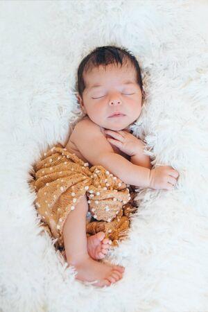 newborn baby sleeps wrapped in a blanket