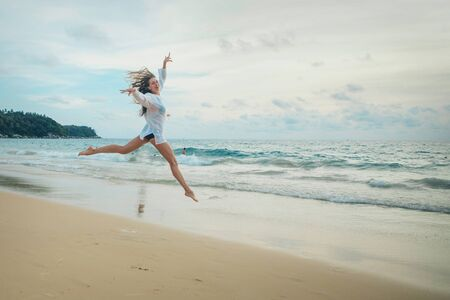 woman jumping happy in the beach with a blue sky and sea in the background