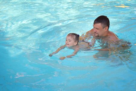 a man with a child swimming in the pool. Dad with daughter in the water