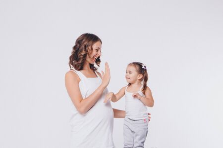mother and daughter slapped each other's hands. Pregnant woman and child negotiate on white background