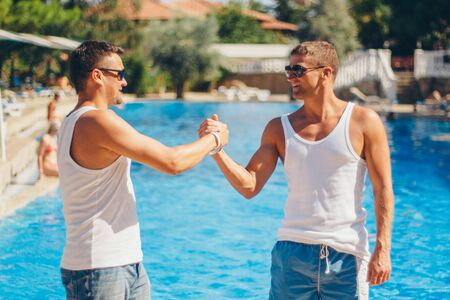 the concept of recreation, tourism - two smiling inflated men with glasses having fun by the pool