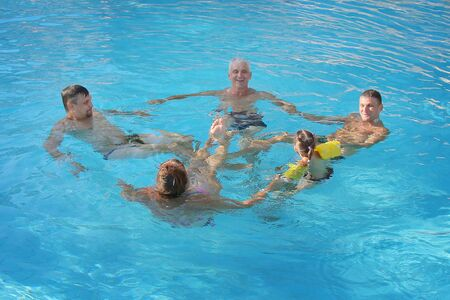 The concept of sports, recreation, healthy lifestyle - 5 people swim in the pool forming a circle. People in the water holding hands