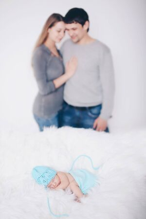 the concept of parenthood, children's Day, medicine, IVF-father and mother looks at the sleeping newborn and stroking it. Isolated on white background. Stok Fotoğraf