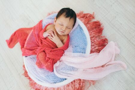 newborn baby wrapped in a blanket sleeping in a basket. concept of childhood, healthcare, IVF Banco de Imagens