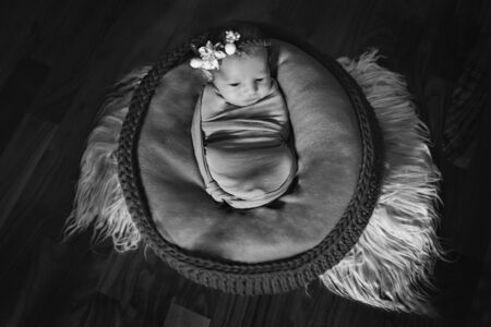 newborn baby with a flower on his head, wrapped in a blanket, sleeping in a basket. the concept of childhood, health, IVF