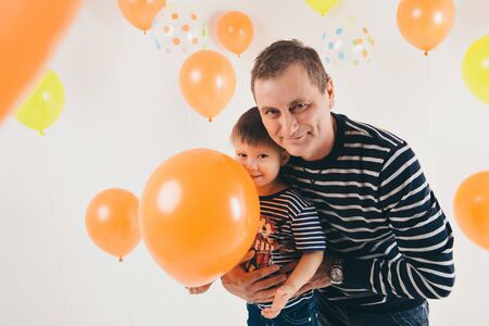 the concept of celebration, fun time spending - family at the party. adults and children on a white background among the colored balls celebrate their Birthday Archivio Fotografico - 129616052