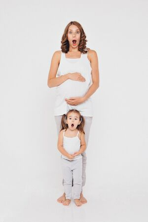 pregnant woman and little girl in sportswear on white background. The girls holds her stomach with her mouth wide open and a surprised expression on her face 写真素材