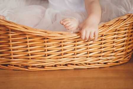 the handle and leg of the child sticking out of a wicker basket. the concept of rest, fun, home comfort, IVF