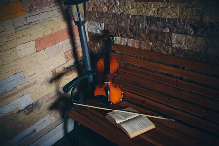 violin, bow and open book on a bench by the stone wall