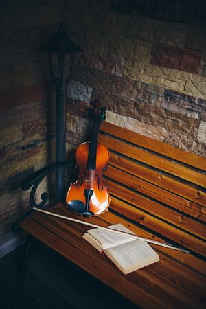 violin, bow and open book on a bench by the stone wall Banque d'images - 129498272
