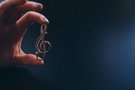 Golden violin key in the hands of women. jewellery: brooch and rings Banque d'images - 129498277