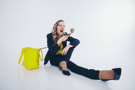 a businesswoman in a black and yellow suit pulls out of a yellow bag phone and yells at him. Beautiful woman sitting on floor on white background. the concept of the work in the office, business plan, fashion