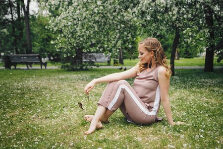 fashionista in dark glasses walking in the Park barefoot. Beautiful girl in nature